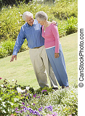Senior couple in garden admiring flowerbed