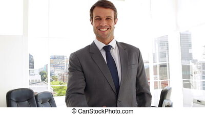 Happy businessman giving thumbs up in his office