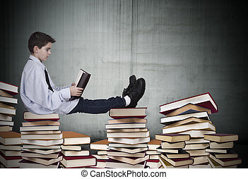 bookstore - boy sitting on stacked books studying with a...