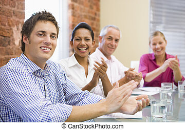 Four businesspeople in boardroom applauding and smiling
