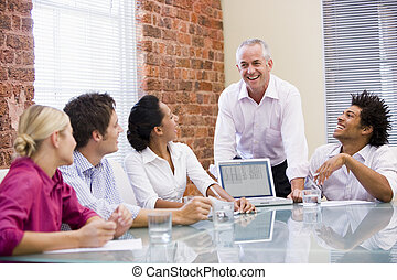 Five businesspeople in boardroom with laptop laughing
