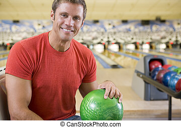 Young man holding a bowling ball in a bowling alley