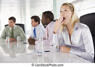 Four businesspeople in boardroom with one businesswoman...
