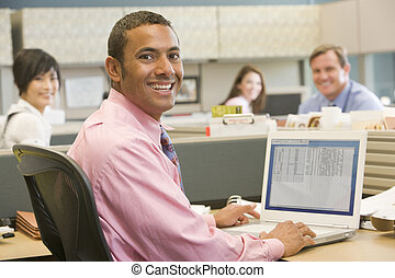Businessman in cubicle using laptop and smiling