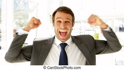 Happy businessman cheering in his office