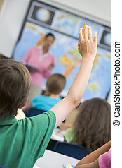 Elementary school pupil asking question in geography class