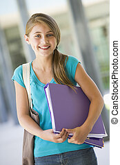 Elementary school pupil outside with folder