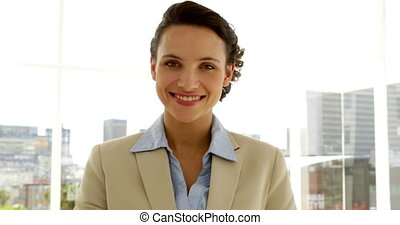 Smiling businesswoman showing her card in the office