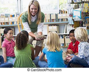 Kindergarten teacher and children looking at bird\\\'s nest...