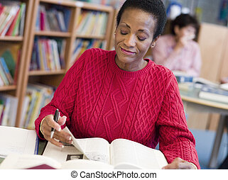 Mature female student studying in library