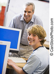 A teacher talks to a schoolboy using a computer in a high...