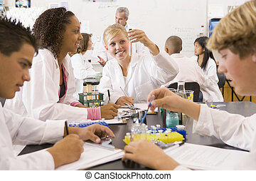 School children and their teacher in a high school science...