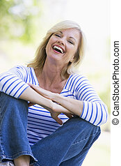 kvinna, sittande, utomhus, skratta