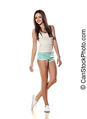 sporty girl - pretty girl in shorts and shirt posing on...