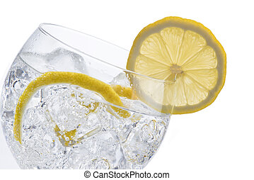 Gin and tonic in a balloon glass garnished with lemon and...