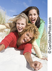 Three female friends having fun at beach