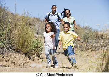 Family running on path smiling