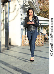 Woman walking in the street writing in a smart phone - Happy...