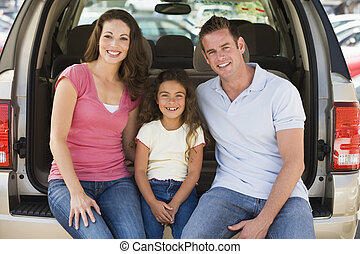 Family sitting in back of van smiling