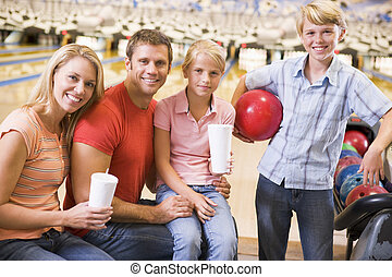 Family in bowling alley with drinks smiling