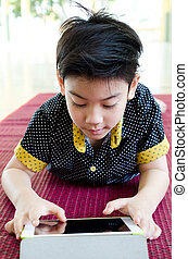 Little asian boy smiles with tablet computer acting on his face