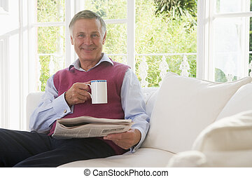 Man in living room with coffee reading newspaper smiling