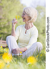 Woman sitting outdoors smiling and holding a Buttercup...