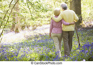 Couple walking outdoors with walking stick