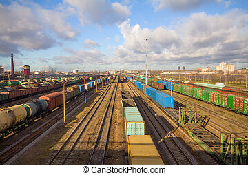 Freight train with color cargo containers passing railway...