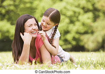 Mother and daughter lying outdoors with flower smiling