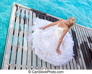The young beautiful woman in a dress of the bride  at edge of the sea