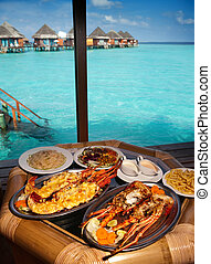 Two plates with lobster on table at window with view on...
