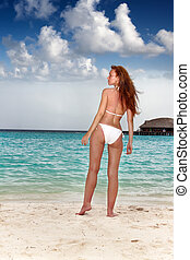 The young beautiful woman on a beach