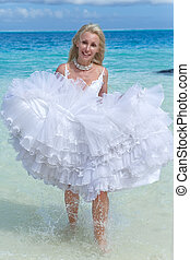 The young beautiful woman in a dress of the bride runs on waves of the sea