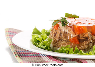 meat aspic - jellied meat with lettuce leaves on a white...