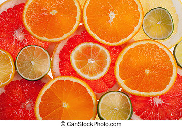 background of different colored slices of citrus fruits close up