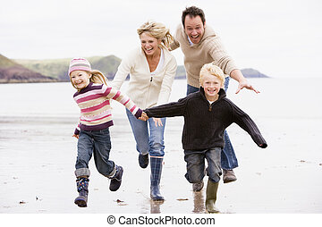 Family running on beach holding hands smiling