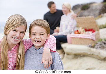 Family at beach with picnic smiling