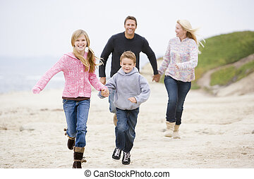 Family running at beach holding hands smiling