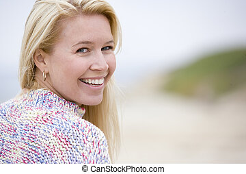 Woman standing at beach smiling
