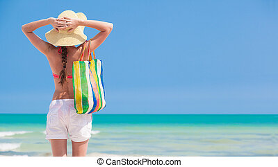 Woman in bikini and straw hat with beach bag standing on...