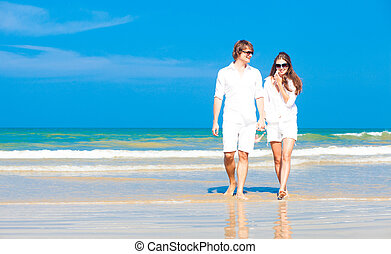 Front view of young happy caucasian couple in white walking on beach looking at the sea