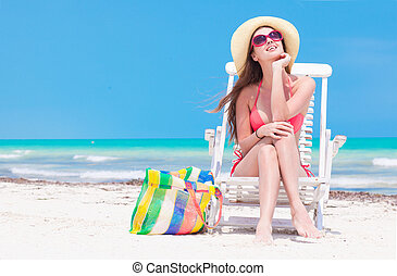 Woman in bikini and straw hat with beach bag sitting on...