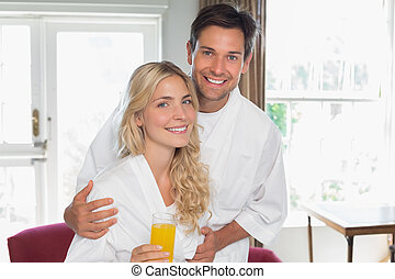 Young couple with orange glass at home