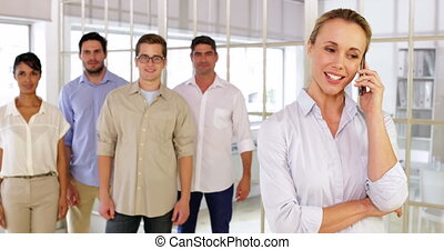Smiling businesswoman phoning while her colleagues pose in...