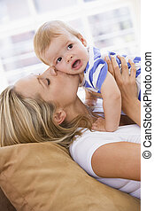 Mother in living room kissing baby