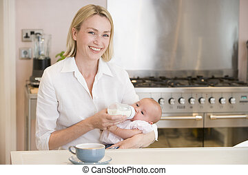 Mother feeding baby in kitchen with coffee smiling
