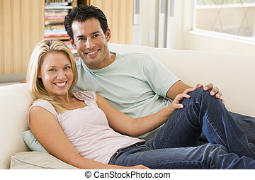 Couple in living room reading newspaper and smiling