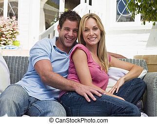 Couple sitting outdoors on patio smiling - man and women...