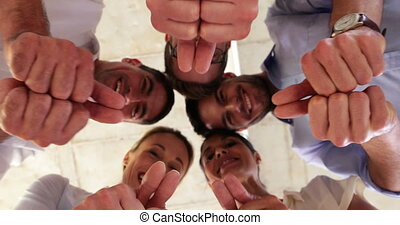Businesspeople showing thumbs up at camera in the office
